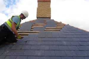 Roofer replacing slates on a pitched roof for Kingsley Roofing.