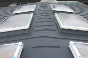 Flat roofing with lead effect, with rooflights